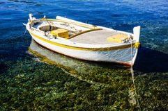 Small rowing boat is anchoring in clear water. Small fishing boat is anchoring in clear shallow water. the boat is reflecting in the water Royalty Free Stock Images