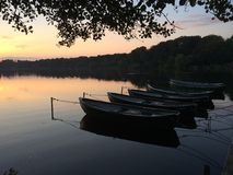 Small Rowing boat on a lake in the sunset. Stock Image