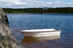 Small rowing boat. Small white rowing boat in sunshine, tied up on the shore of a lake in Sweden Royalty Free Stock Image