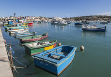 Small rowing boats at Marsazlokk harbour on Malta. Small rowing boats at Marsazlokk harbour on Malta during the Sunday Market, with larger boats and town in Stock Photos
