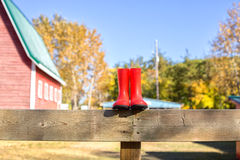 Small rubber boots perched on wood fence Stock Images