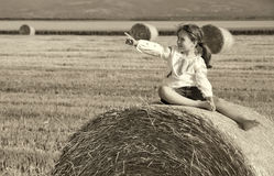 Small rural girl on the straw after harvest field with straw bal Stock Images