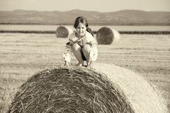 Small rural girl on the straw after harvest field with straw bal Stock Photo