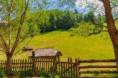 Small rural huts in the middle of green meadows in the mountains stock photo
