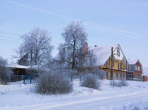 Small russian village view on frosty winter day with many snow. Small russian village on frosty winter day with clear blue sky Royalty Free Stock Photography