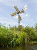 Small and rusted old metal windmill at the waterside Royalty Free Stock Photo