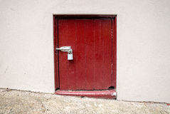 Small rustic old vintage door with padlock on pavement Stock Photo
