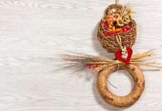 Rustic Ornamental Wicker Basket on a White Wooden Background. Small rustic ornamental wicker basket full of dried flowers and enriched with other decorations Royalty Free Stock Photo