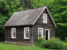 Small rustic wood house in trees. Small unpainted, natural dark wood rustic house, with trees and bushes Royalty Free Stock Photography