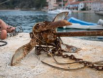 Small rusty anchor with chain lying on the ground. Croatia Stock Photo