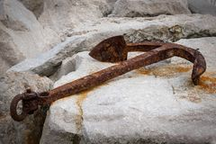 Small rusty anchor lying on rocks in a harbor. Croatia Stock Images