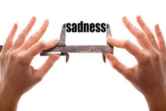 Small sadness. Color horizontal shot of two hands holding a caliper and measuring the word sadness Stock Photography