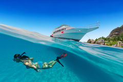 Small safari boat with snorkeling woman underwater. Stock Photos