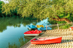Small sail and pedal boats parked by river bank at summer sunset. Water attractions and water vehicle rental service in park. Small sail boat and colorful pedal Stock Image