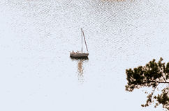 Small sailboat. Alone, floating sailboat on a lake Royalty Free Stock Photos