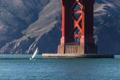 Small Sailboat at base of Golden Gate Bridge Stock Image