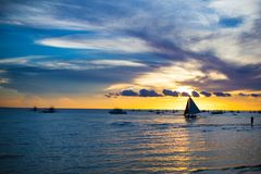 Small sailboat on the beautiful sunset in the Royalty Free Stock Photos