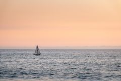 Single sail boat sailing on sea during an orange sunset royalty free stock photos