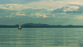 A small sailboat floats on the reservoir stock photo