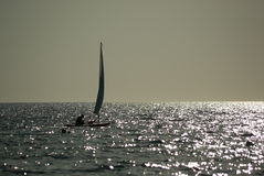 Small sailboat sailing on calm sea at sunset. A small sailboat on the calm sea at sunset just sailing away Royalty Free Stock Images