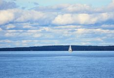 Small sailboat on the sea sailing to the horizon in summer Stock Photos
