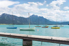 Small sailboats anchoring in alpine lake, landing stage and mountains. Royalty Free Stock Photo