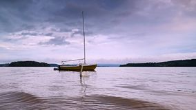 Small sailing boat anchoring next to a buoy in the calm water of lake. Moody tones stock video footage