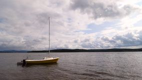 Small sailing boat anchoring next to a buoy in the calm water of lake. Moody tones stock video