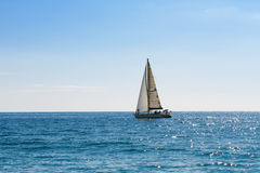 Small sailing boat in blue and calm sea Stock Photos