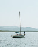Small sailing boat on calm sea with hills. Small sailing boat anchored on calm sea with hills in background during summer Royalty Free Stock Photo