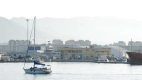 Small sailing boat navigating a harbor stock footage