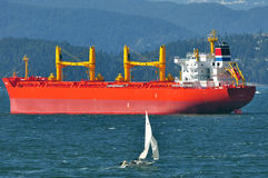 A small sailing boat passing a big ship Stock Photos