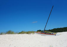 Small sailing boat on the sand dunes. Peaceful morning on the beach. А small sailing boat lies on the sand dunes of white. US East Coast Stock Image