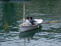 Small sailing boat with two rowers. Bermeo. Small white sailboat with two rowers with two rowers in the port of Bermeo Stock Photography