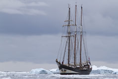 Small sailing ship in Antarctic waters between ice floes and ice. Bergs Stock Photography