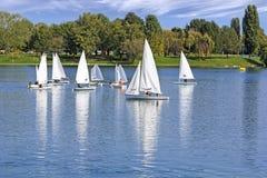 The small sailing ships regatta on the lake. The small sailing ships regatta on the blue lake stock photography