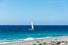 A small sailing yacht floating on the sea. Royalty Free Stock Image