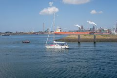 Small sailing yacht sails out of IJmuiden seaport towards the No. Rth Sea. At the background a bulk carrier and a steel plant Royalty Free Stock Photo