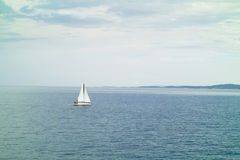 A small sailing yacht in the sea Stock Photo