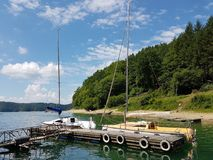 Small sailing yachts of coastal navigation are moored at the pier in a picturesque harbor. Prestigious and healthy lifestyle. Recr stock images