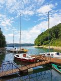 Small sailing yachts of coastal navigation are moored at the pier in a picturesque harbor. Prestigious and healthy lifestyle. Recr royalty free stock photos