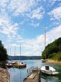 Small sailing yachts of coastal navigation are moored at the pier in a picturesque harbor. Prestigious and healthy lifestyle. Recr royalty free stock images
