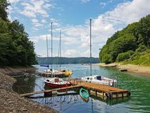 Small sailing yachts of coastal navigation are moored at the pier in a picturesque harbor. Prestigious and healthy lifestyle. Recr stock photo
