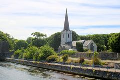 Small church by river. The small Saint Patricks church and Glenarm River in Glenarm in County Antrim in Northern Ireland stock photo