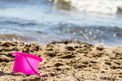 Small sand pail toy on summer beach. Holiday vacation royalty free stock image
