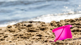 Small sand pail toy on summer beach. Holiday vacation stock photos
