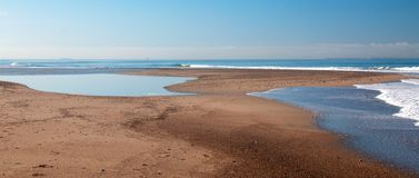 Small sandbar where the Pacific ocean and the Santa Clara river meet at Surfers Knoll beach in Ventura California USA. Small sandbar where the Pacific ocean and royalty free stock image