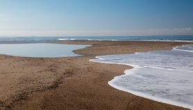 Small sandbar where the Pacific ocean and the Santa Clara river meet at Surfers Knoll beach in Ventura California USA. Small sandbar where the Pacific ocean and stock photos