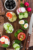Small sandwiches on wooden background. Royalty Free Stock Images