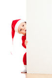 Small Santa baby looking behind placard bannere Stock Photo